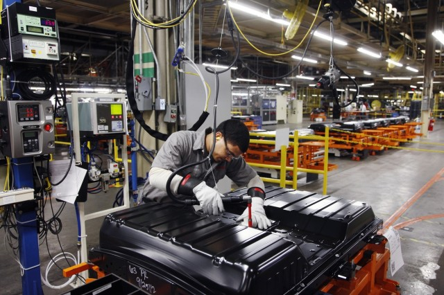 Technician secures cover on ithium-ion battery pack at Nissan plant in Smyrna, Tennessee
